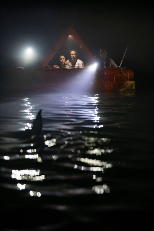Two people huddle with torches in a boat at night, and the fin of a shark protrudes from the water nearby