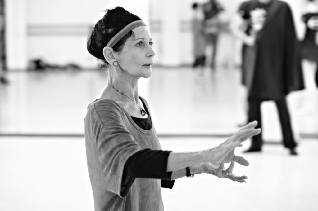 A black and white photo of Lucette. She looks to be in her 60s and is dressed in rehearsal clothes. She is in a studio and appears to be giving feedback or an instruction to a dancer.