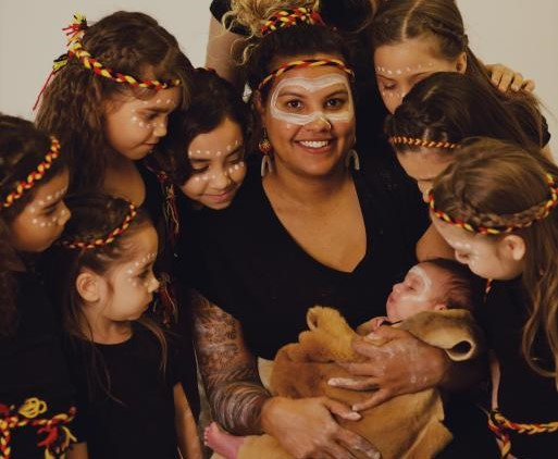 A group of children gather around a woman holding a baby, all are painted with white paint and wearing headbands in red, black and yellow braid