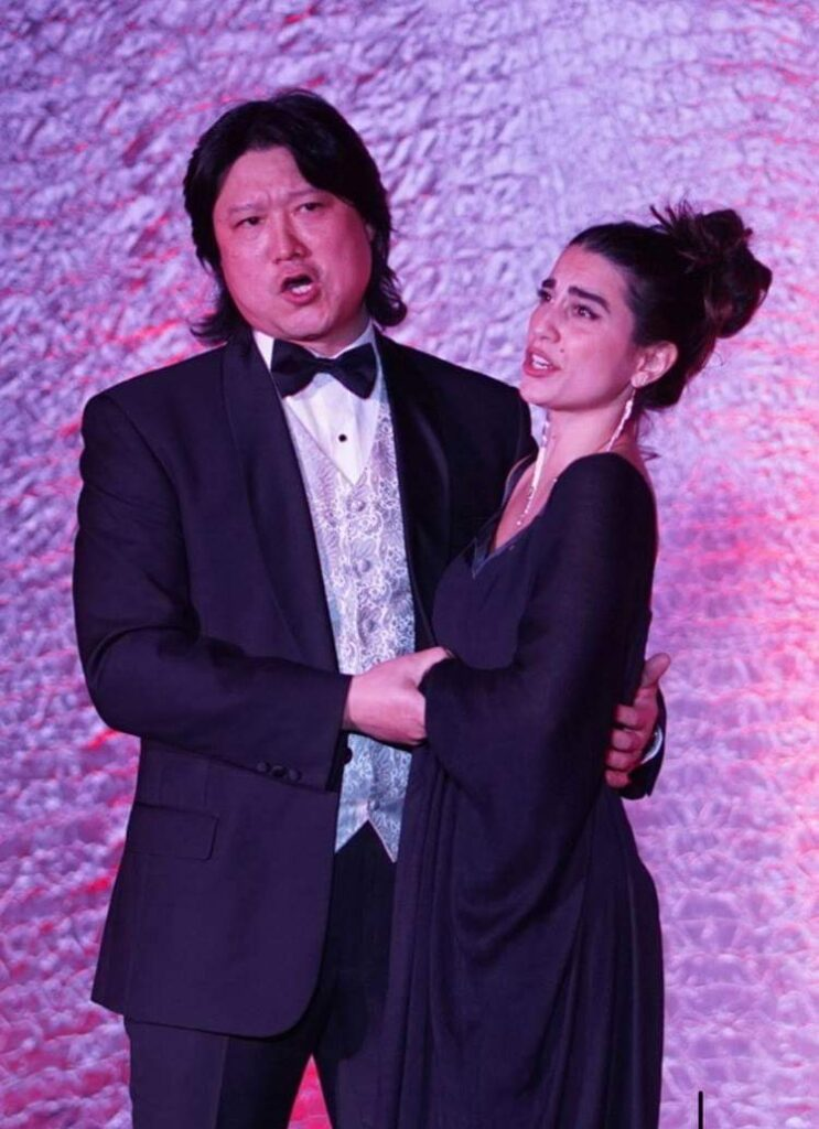 A man in a suit  sings to a lady wearing a black dress