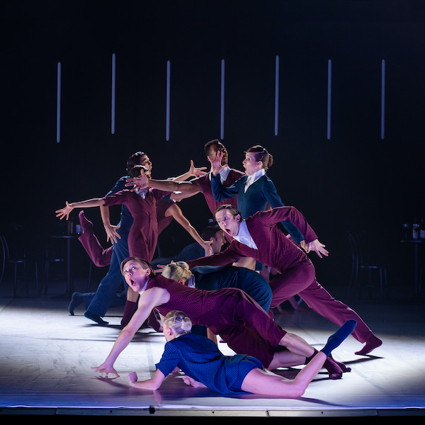 A group of eight dancers are clustered together, in exaggerated poses. Some have their arms outstretched, one is lying on the floor, one appears to be tripping. All appear to be mid motion and have expressions of exaggerated surprise on their faces.