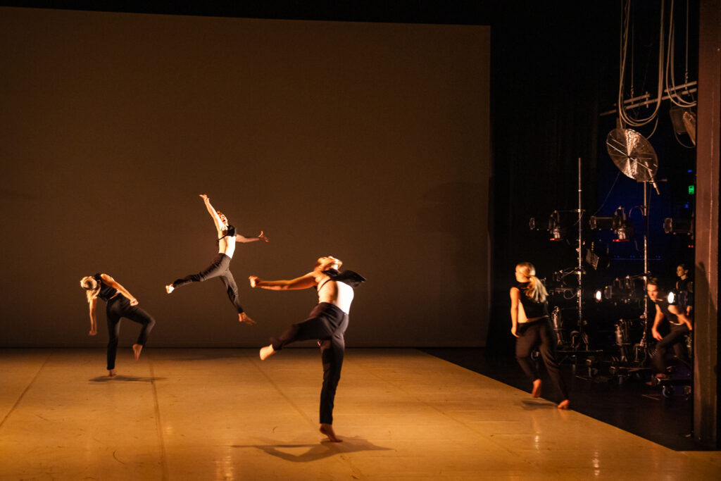 Four dancers are on stage, captured mid movement. Two stand on one leg, leaning precariously, their backs arched. One flies in the air, arms and legs outstretched. Another is mid stride.