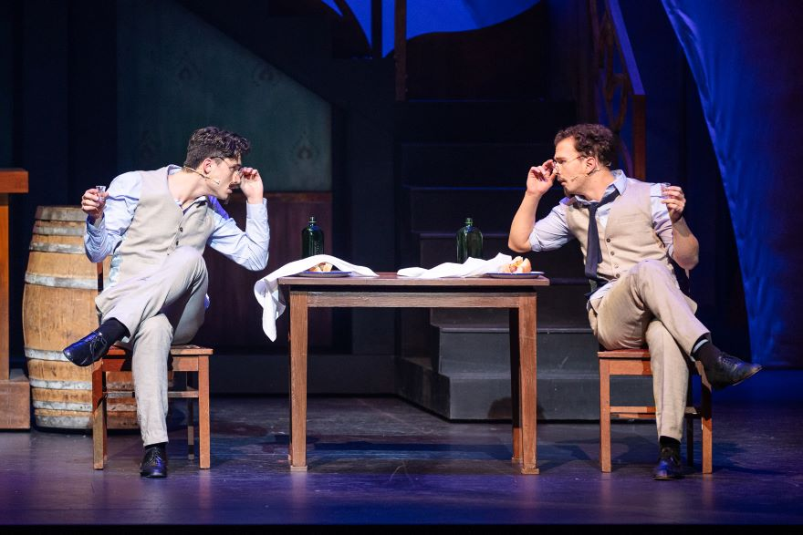 Two men in cream suits peer across a table at each other, over their glasses.
