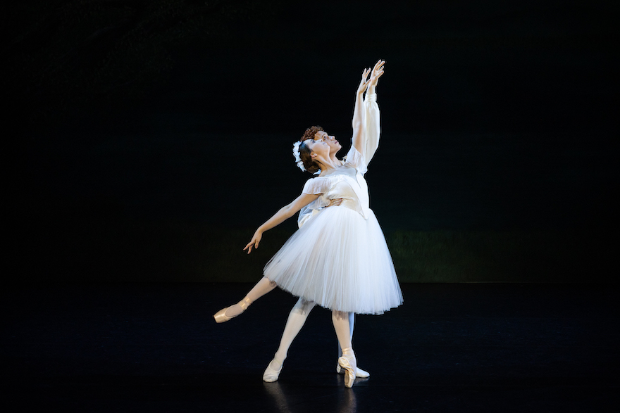 A male and female ballet dancer - she holds an arabesque, he stands behind her supporting her. Both wear white, she is in a tutu.