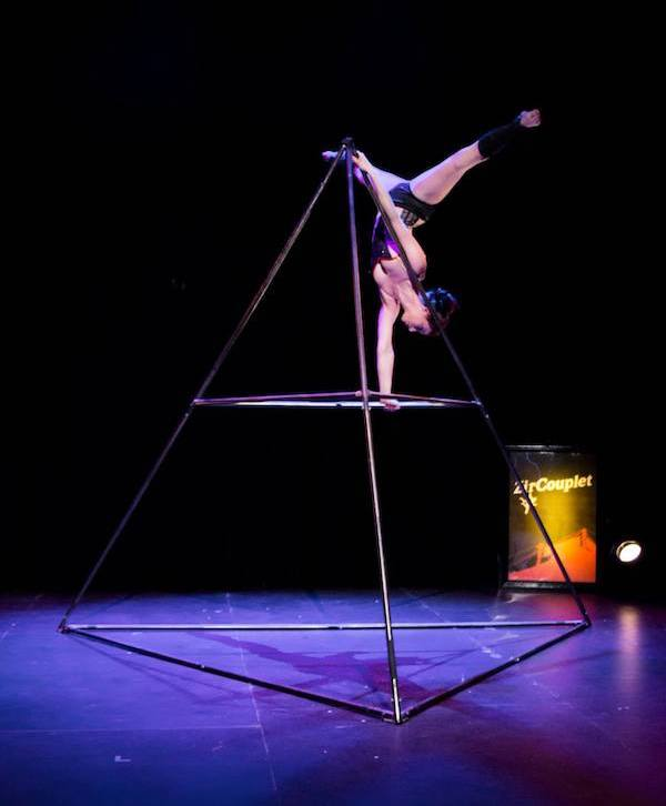 A circus artist performs a handstand on a pyramid shaped apparatus. Her legs are in a straddle position. She wears black underwear and black leg warmers.