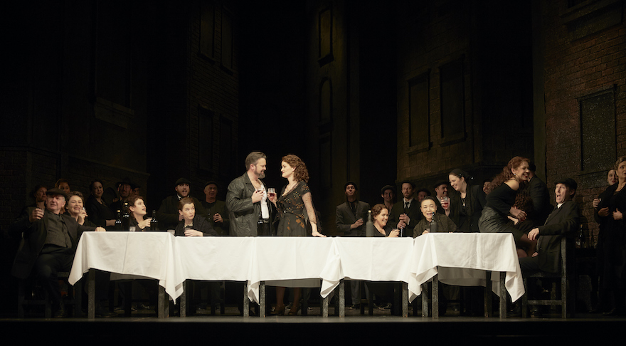 The cast of 'Cavalleria Rusticana' sit at a long table, in the middle stand Paul O'Neill and Brigitte Heauser, each holding a glass of wine.