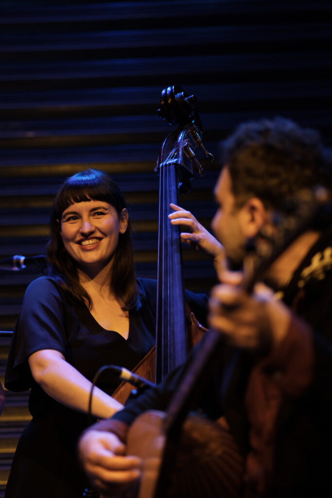 A close up of Kate Pass playing bass. She is smiling at another musician who is out of focus in the right corner of the photo. We can see that he's looking at her, and he is playing what looks like a lute.