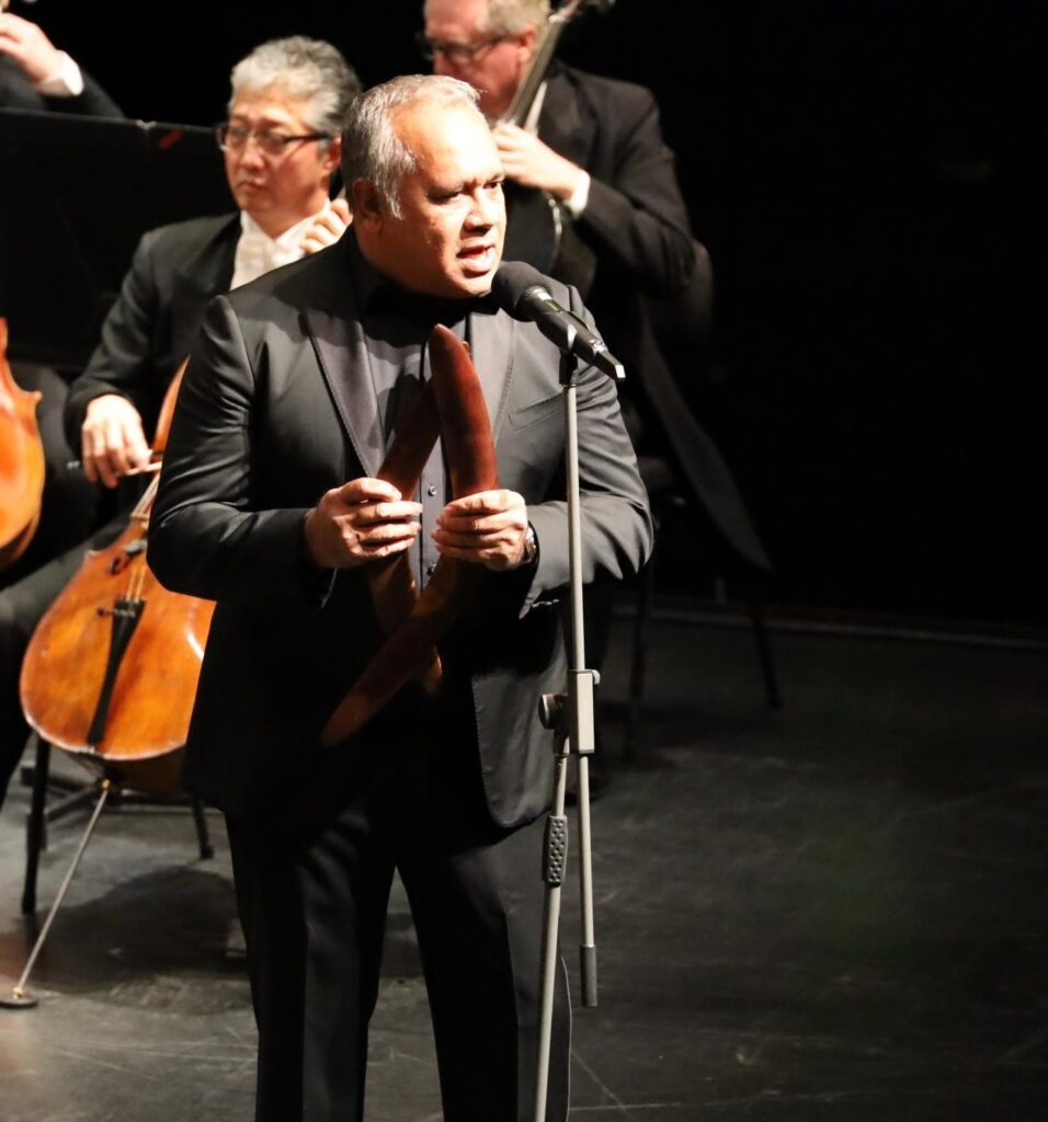 A Noongar man sings in front of an orchestra