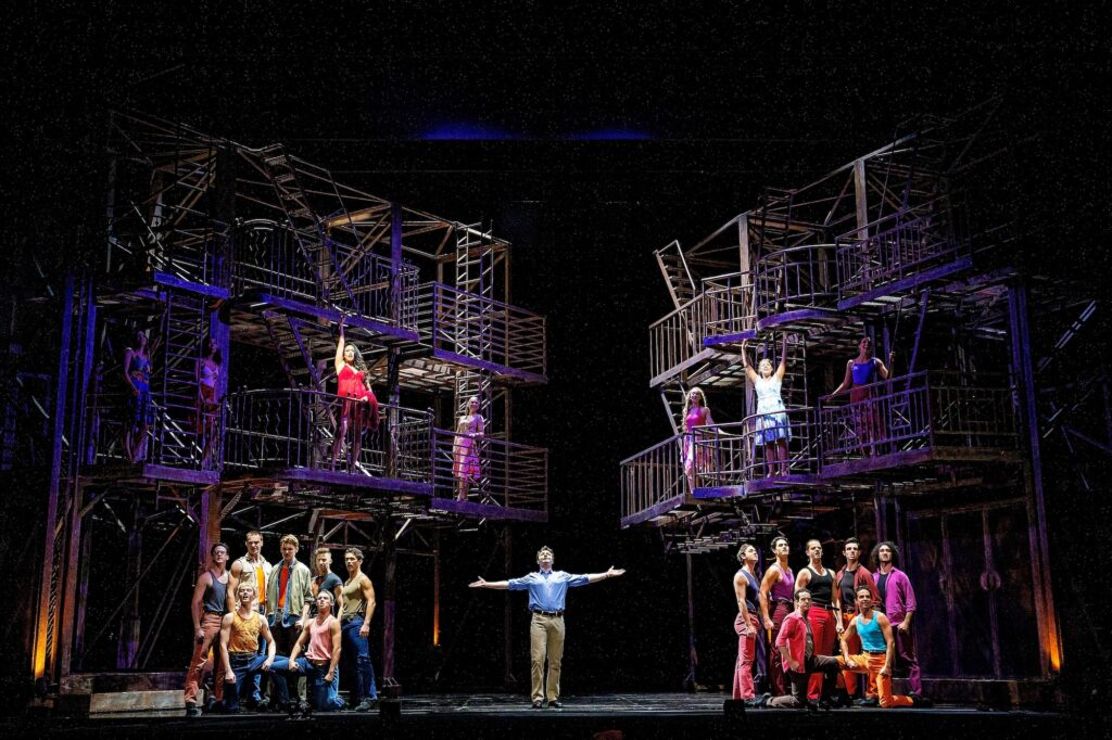 A single male cast member stands in the centre of the stage his arms outstretched; on either side are two groups of male performers. All are casually dressed in jeans, shorts and singlets. Several women watch from scaffold-like balconies.