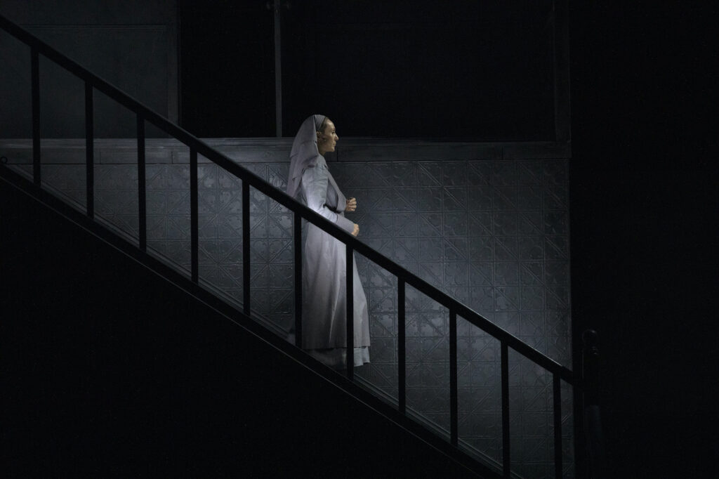 A matron descends a staircase in the semi-darkness. The wall behind her is made of pressed tin.
