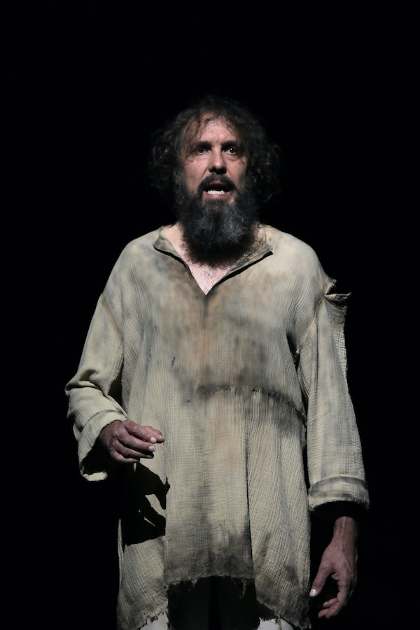 Maitland Schnaars is dressed in ragged, dirty clothes. His hair is shaggy and he has a long beard. He is mid-speech, one arm slightly raised.