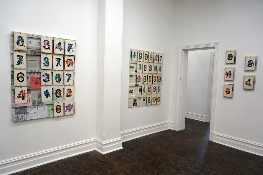 Tin score plays hand in rows and columns, each with a single digit number and an image of a woman playing football superimposed on top. Behind the plates are what look like newspaper articles.