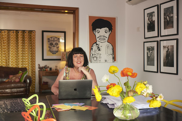 Paula Hart sits at her dining room table, at home. The room is brightly coloured, with accents of orange and yellow lifted by a vase of orange and yellow flowers in the foreground.