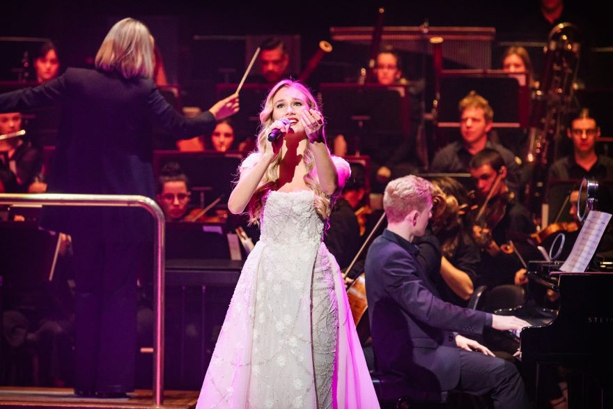 A woman in white princess dress and long golden hair sings in front of an orchestra