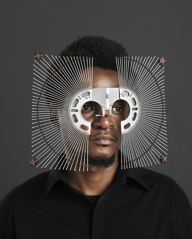 A man of colour wears a mask that is made of strands of metal that fan outwards from goggle-like flattened metal that frames his eyes.