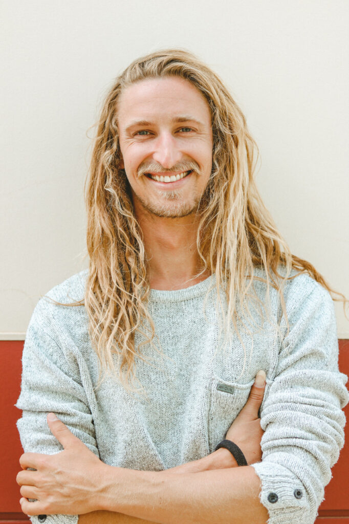 A man with long blonde hair stands smiling with sleeves rolled up