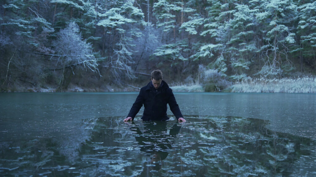 A man standing in an icy green lake against a backdrop of startlingly green foliage,