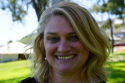 A headshot of Dawn Jackson. She is a woman in her 50s, with blonde shoulder length wavy hair, blue eyes and a big smile. The background is out of focus and she seems to be standing in a suburban park - you can see grass and houses in the background. Although the sun is out she is in shadow.