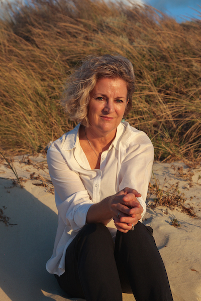 Karen Herbert sits on the sand. Behind her is coastal scrub. The has bobbed blonde hair that is blowing in the wind and wears a casual white shirt and black pants. Her hands are clasped and rest on her bent knees. She looks directly at the camera with a slight smile.