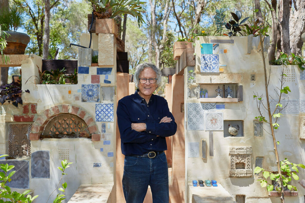Leon Pericles stands in front of a large scale sculpture in his Margaret River garden, The sculpture is made up of walls decorated with colourful tiles and plants. He is smiling.