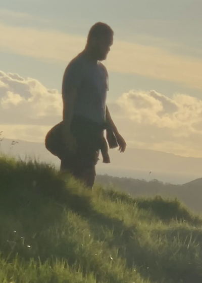 A man stands on a grassy slope, gazing downwards. He is bathed in gentle sunlight that casts his face in shadow. The light has a bleached quality. In the background we can see the outlines of mountains.