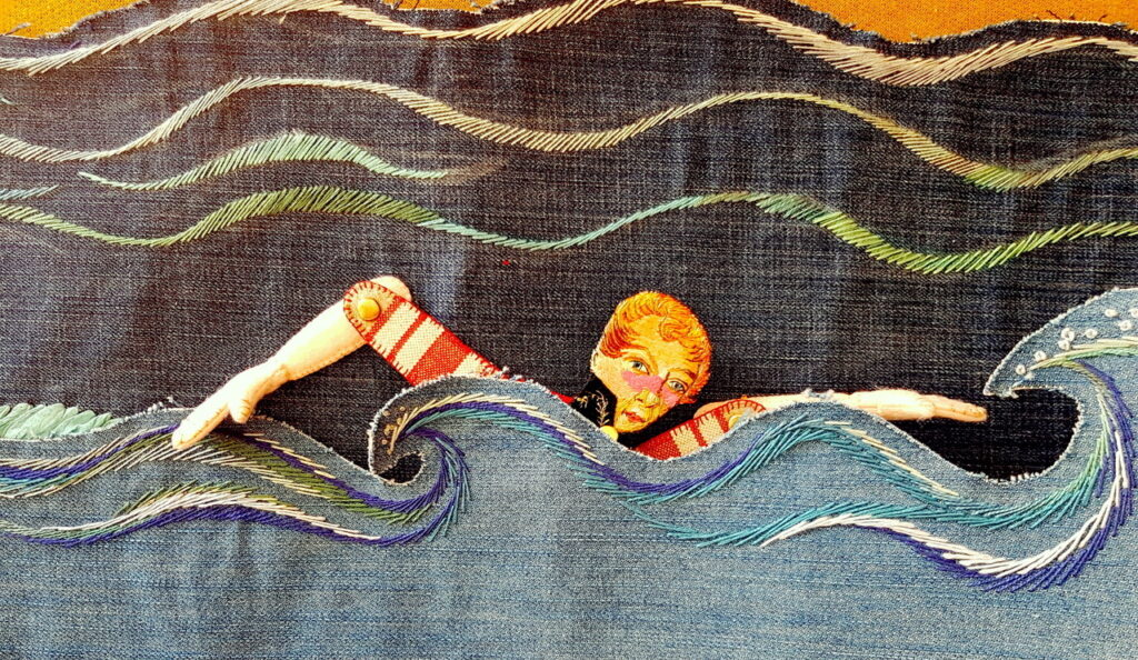 An image of a swimmer doing freestyle through the ocean, made of a collage of different fabrics.