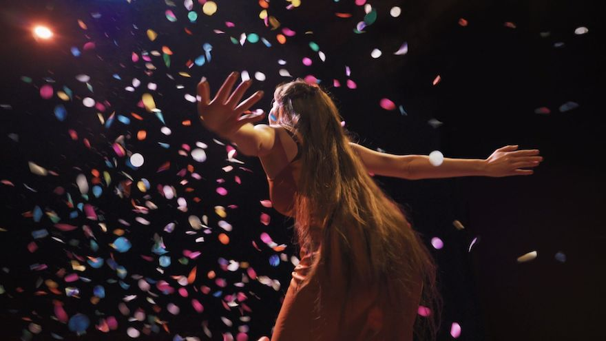 A woman with long hair and outstretched arms faces a shower of colourful confetti. We can't see her face.