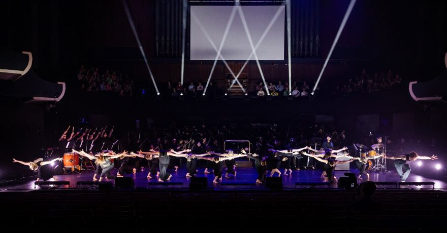 Black-clad dancers dip forward with hands outstretched behind, lit by thin shards of white light