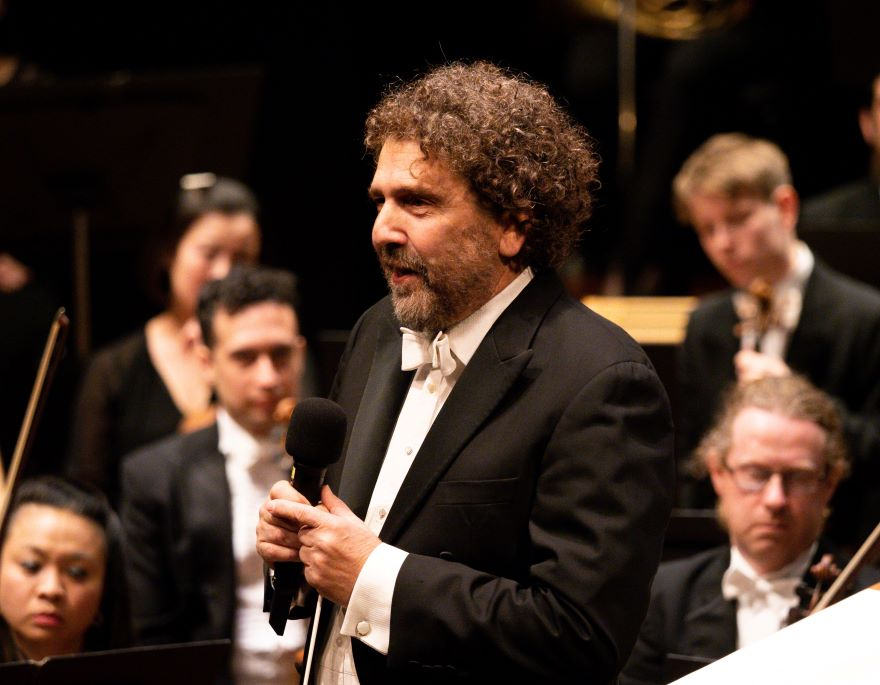 A man in a tuxedo holds a mic and an orchestra sit behind him