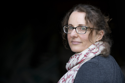 A headshot of Zoe Deleuil. She is positioned at right angles to the camera and turns her head to the lens. She has wavy hair tied back, with some strands left out to frame her face. She wears glasses, a white scarf with a red pattern and a grey top.