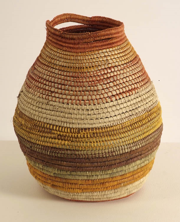 A woven basket in warm shades of earth toned oranges, yellows and browns. The shape is like a vase, narrower at the top and bottom, and wider in the middle.