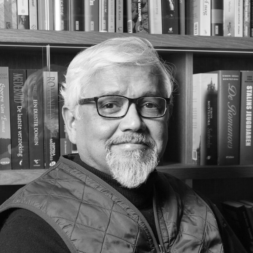A black and white photo of a man wearing glasses, sitting in front of a bookshelf