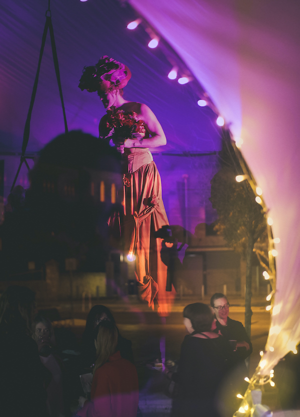A performer on stilts wanders amongst people eating food inside a tent lit with fairy lights.