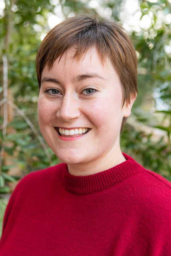 A headshot of a young woman, with cropped auburn hair, smiling at the camera. She wears a red knit sweater.