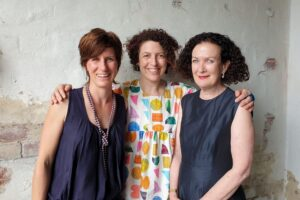 Three women standing close together against a partially rendered white wall