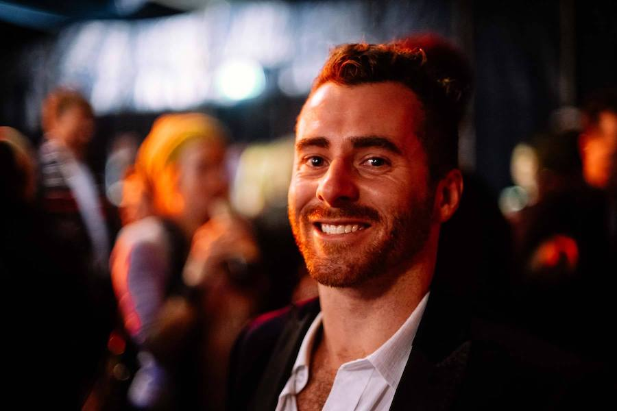 A man with reddish hair smiles at the camera. His hair is long and tied back in a high bun. The background is out of focus but we can see people,  including a woman holding what might be a bottle to her mouth, and lights. It looks like it is night time.