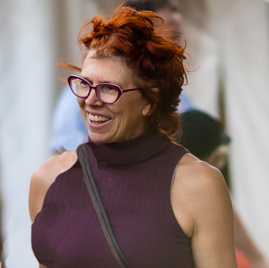 A head shot of a woman with red hair. She is looking at someone or something to the left of the frame and smiling. She wears violet rimmed glasses and a muted violet sleeveless ribbed top with a high neck.