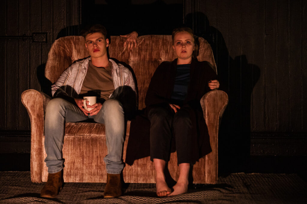 Two young people sit on a sofa in the semi-dark. A hand appears over the sofa back. It looks. creepy.