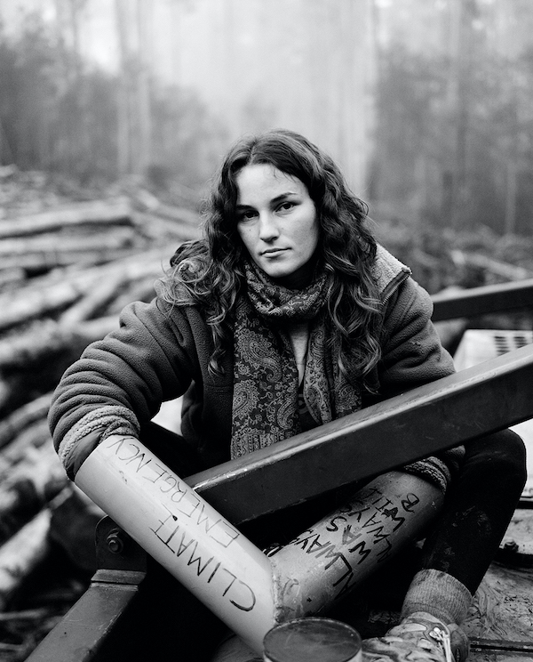 """A black and white photo of a  young woman sits amidst some iron bars. In the background we can see logs. On her arms are plastic tubes that say """"climate emergency"""" and """"always was always will be"""". She looks directly at the camera, her expression calm and serious."""