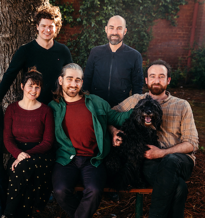 A group of five people posed for a photograph. Two stand behind, three sit in front. A dog sits on the lap of the man in the front right of the frame, the man next to him pats the dog. Everyone is smiling, including the dog. The photograph is outside, a tree trunk is visible in the left of the frame and behind is a redbrick wall partially covered in a creeper.