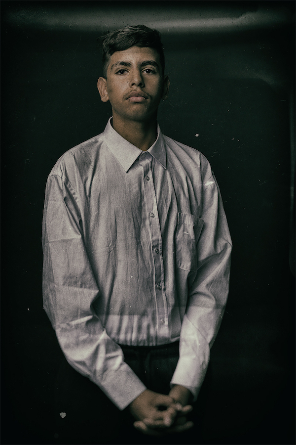 A colour photo of a young First Nations man. He is wearing a white button down shirt and black pants, and posed for the portrait.