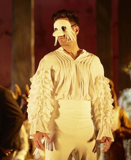 a male performer in a white bird costume, with a mask for a beak and sleeves that look like feathers