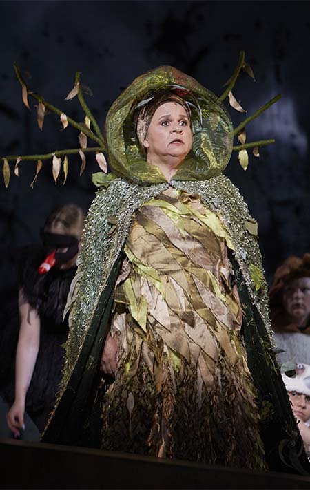 A female performer dressed in an elaborate costume that looks to represent a tree with a dress made from leaves, a green hood and a flowing cape