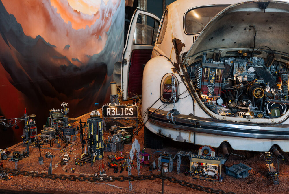 RELICS by Jackson Harvey and Alex Towler, image courtesy of Scribblers Festival and FORM, photo by Taryn Hays 9 A scene from Relics in which lego machines have been built into the boot of an old VW Beetle. The car sits on red dirt and pebbles, on which various lego machines are built. The feel of the scene is industrial and dystopian. Minifigs rule the world!
